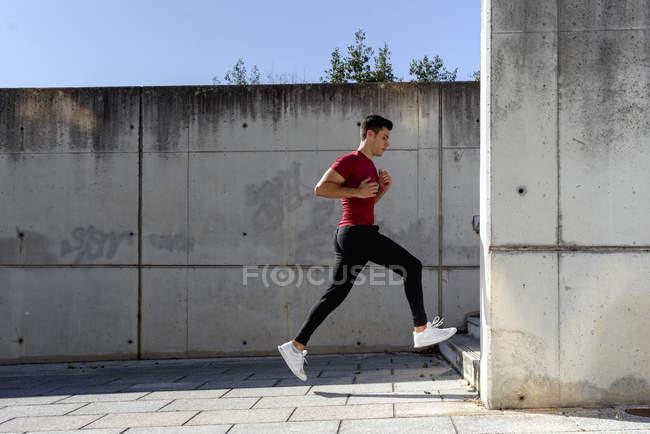 Чоловік у червоній сорочці і чорні штани бігають по сходах під час тренувань у сонячний літній день у місті — стокове фото