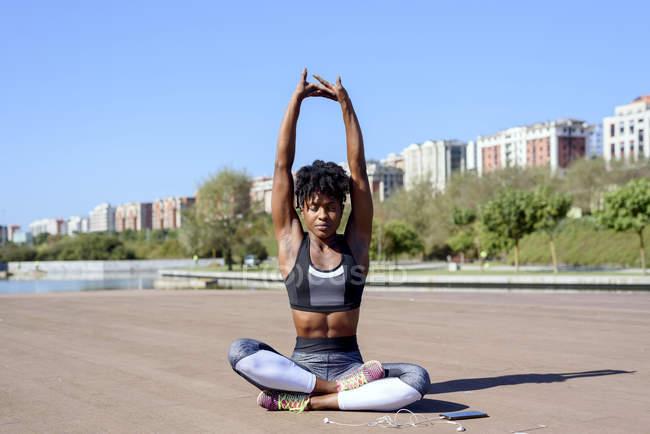 Афроамериканка в спортивном топе и ногах, сидящая в позе лотоса и растягивающая руки вверх, расслабляясь — стоковое фото