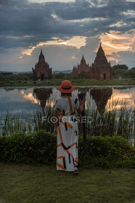 Woman standing at lakeside and enjoying view of Buddhist temples — Stock Photo