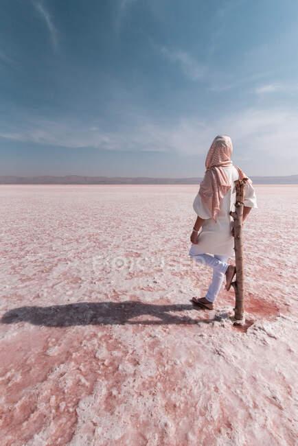 Thoughtful relaxed tourist enjoying unusual scenery of pink salt lake — Stock Photo