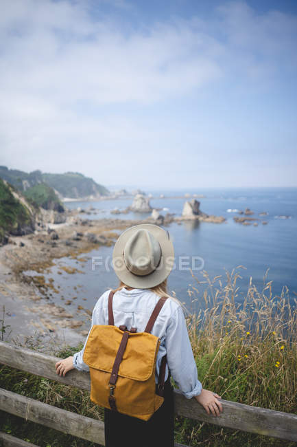 Back view of female traveler in hat and backpack leaning in wooden fence on hilltop while looking into sea distance in Asturias, Spain — Stock Photo