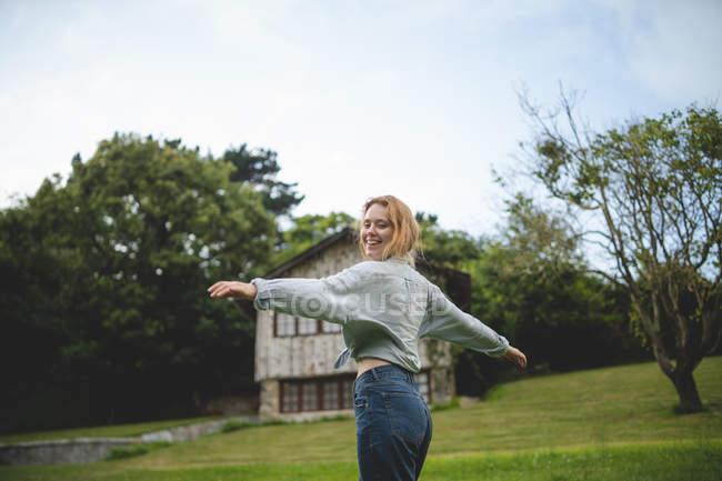 Vista laterale della donna che balla godendosi una passeggiata sul prato verde vicino alla casa in legno nel villaggio rurale delle Asturie, Spagna — Foto stock