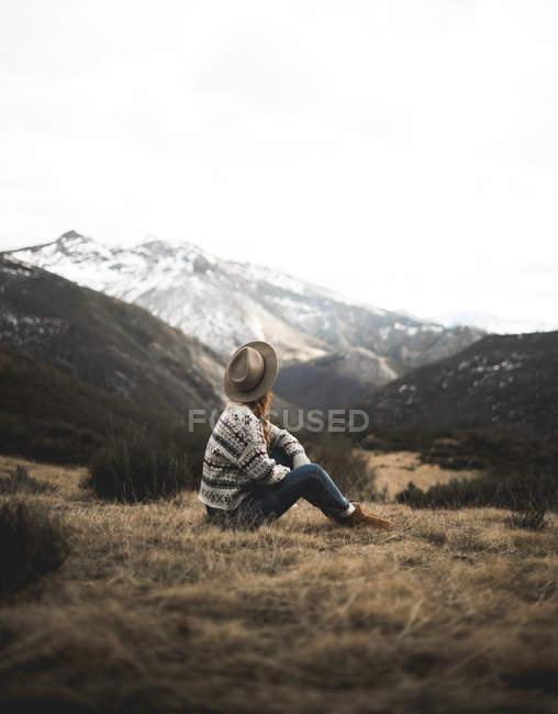 Vista laterale della donna in cappello che distoglie lo sguardo sulle montagne mentre riposa sull'erba marrone delle Asturie, Spagna — Foto stock