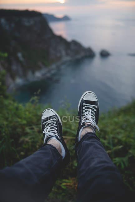 Immagine ritagliata dell'uomo seduto sul bordo della collina sullo sfondo di panoramico paesaggio marino delle Asturie, Spagna — Foto stock