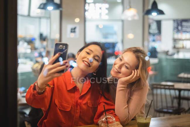 Jovens mulheres tomando selfie no café — Fotografia de Stock