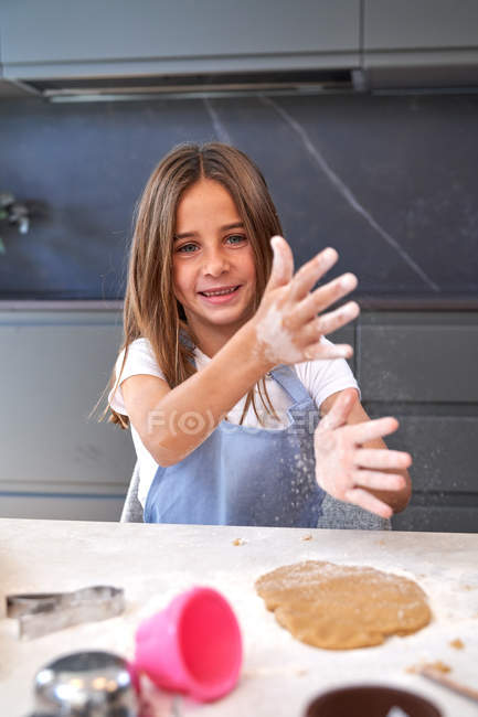 Pleased little girl in apron brushing dirty hands with flour above brown dough and looking in camera at modern kitchen — Stock Photo