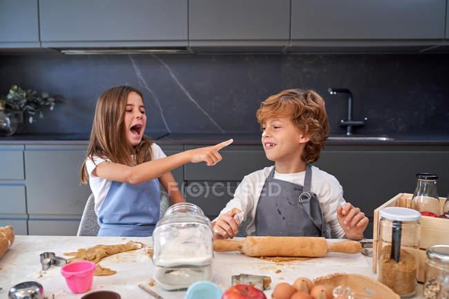 Menino e menina tocando narizes uns aos outros com os dedos com farinha e rindo da cozinha moderna — Fotografia de Stock
