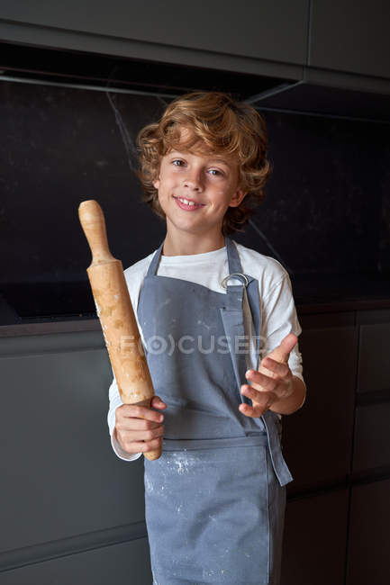 Cute kid in apron standing with rolling pin in hands, smiling and looking in camera at stylish kitchen — Stock Photo
