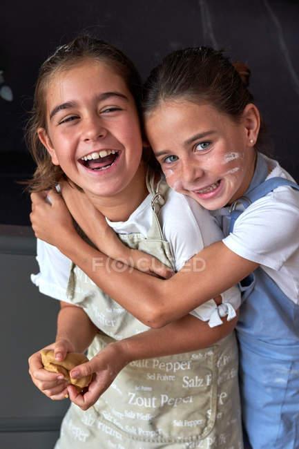 Маленькие девочки с грязными щеками в фартуках смеются и улыбаются, стоя в объятиях и глядя в камеру на кухню — стоковое фото