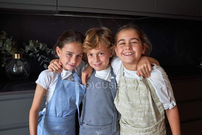 Малі діти з брудними щоками в фартухах сміються і посміхаються, стоячи в обіймах і дивлячись в камеру на кухні — стокове фото