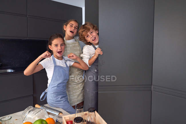 Pequeños niños divertidos masculinos y femeninos en delantales que se divierten mientras buscan ingredientes en el armario en la cocina moderna - foto de stock