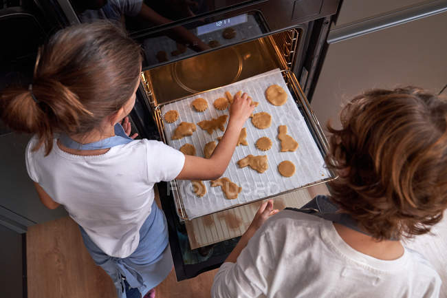 From above children spreading cookies on cookie sheet in oven at modern kitchen — Stock Photo