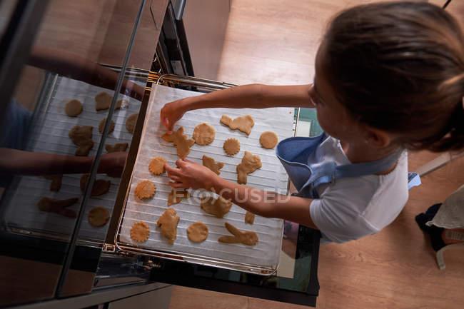 De cima pequena menina em pé avental e colocando biscoitos no forno na cozinha moderna — Fotografia de Stock