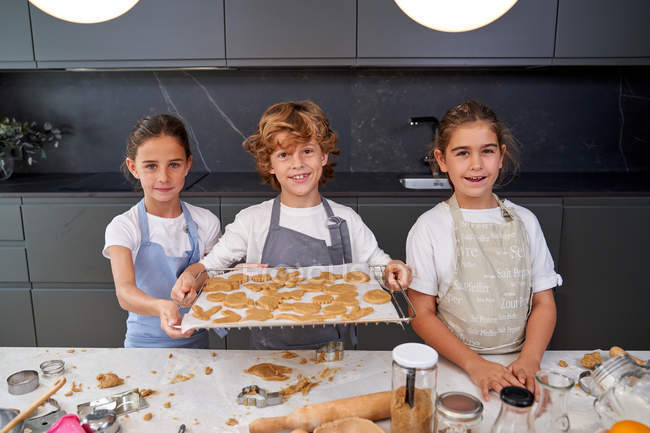 Children in aprons holding tray with cookies ready to put into oven at modern kitchen — Stock Photo