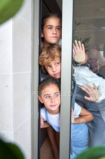 Curious little brother with sisters peering from glass door at home — стоковое фото