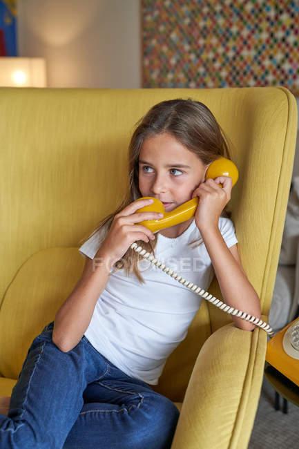 Petite fille en t-shirt blanc et jeans assis sur un fauteuil confortable jaune et parlant sur un téléphone poussiéreux, regardant ailleurs — Photo de stock