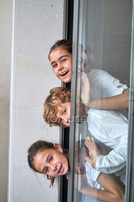 Curioso hermanito con hermanas mirando desde la puerta de cristal en casa - foto de stock