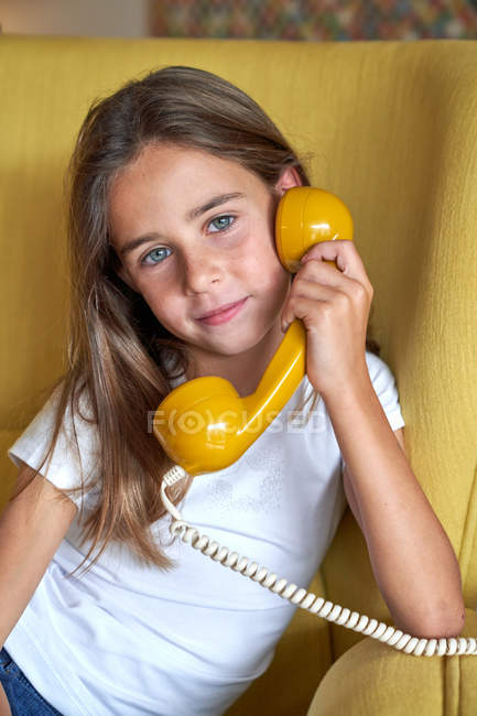 Little girl in white t-shirt sitting on yellow comfortable armchair and talking on fusty telephone, looking in camera — Stock Photo