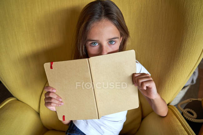 From above of smart girl with blue eyes sitting in yellow armchair while covering face with book and looking in camera — Stock Photo