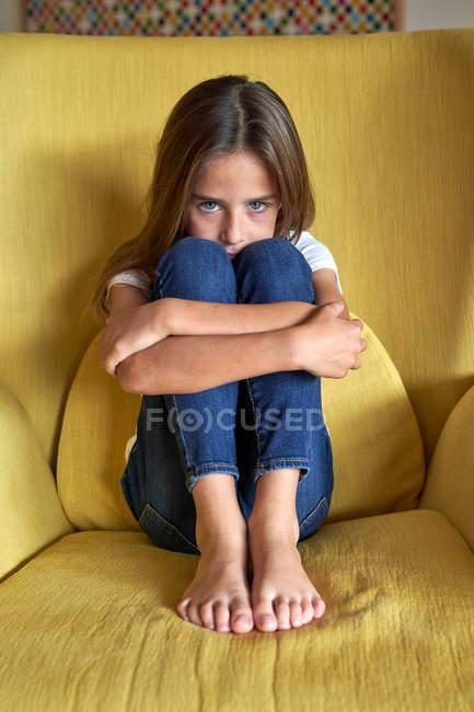 Trauriges kleines Mädchen greift nach Beinen auf gelbem Sessel und blickt in die Kamera — Stockfoto