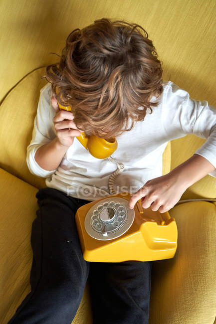 From above little boy sitting on yellow comfortable armchair and talking on fusty telephone — Stock Photo
