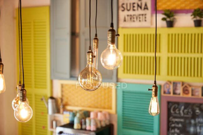 Bunch of pendant lamps against colorful wall in cafe — Stock Photo