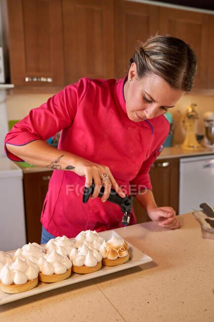 Chef using kitchen mini gas torch while baking meringue in modern kitchen — Stock Photo