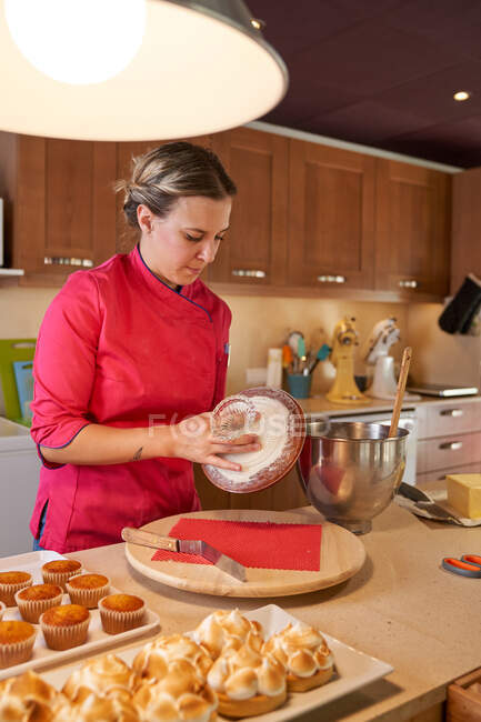 Pensive female cook stacking cake biscuits at home — Stock Photo