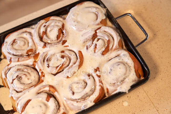 Delicious homemade rolls with icing on baking tray — Stock Photo