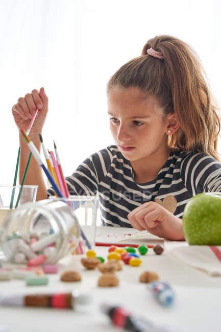 Ernstes kleines Mädchen mit Pferdeschwanz, das am Tisch sitzt und zu Hause vor weißem Hintergrund malt — Stockfoto