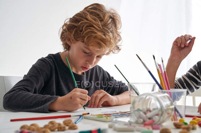 Little boy with curly hair smiling while sitting at table and painting against white wall at home — Stock Photo