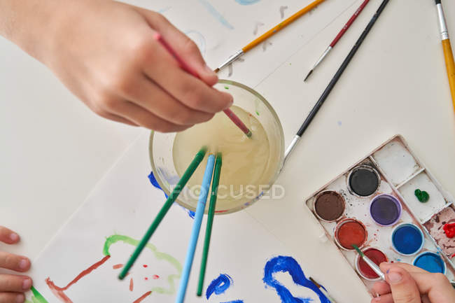 From above unrecognizable children painting on paper while sitting at table at home — Stock Photo