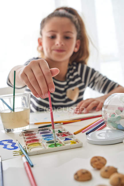 Little girl taking watercolor with brush while sitting at table and painting at home — Stock Photo