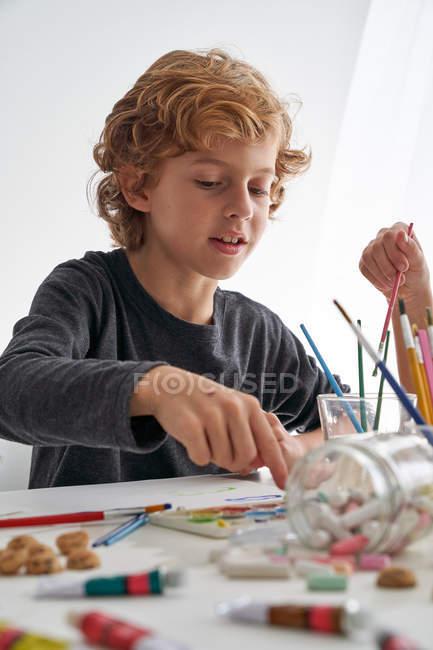 Menino com cabelo encaracolado sorrindo enquanto sentado à mesa e pintando contra a parede branca em casa — Fotografia de Stock