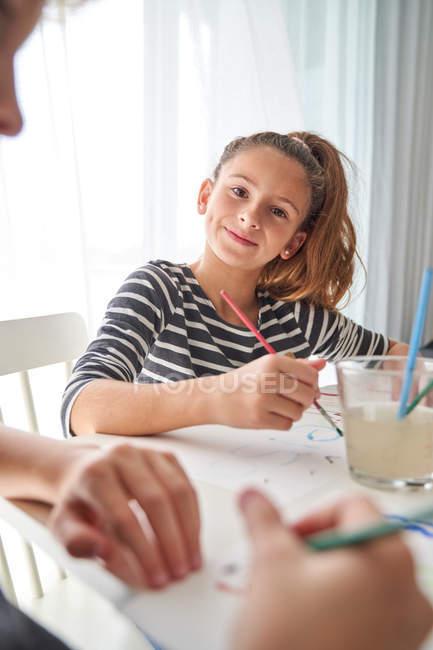 Ernstes kleines Mädchen mit Pferdeschwanz, das in die Kamera schaut und denkt, während es am Tisch sitzt und malt — Stockfoto