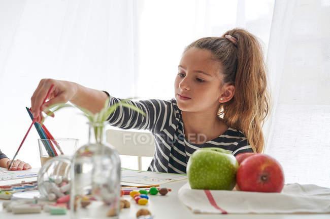 Ernstes kleines Mädchen mit Pferdeschwanz, das wegschaut und denkt, während es am Tisch sitzt und malt — Stockfoto