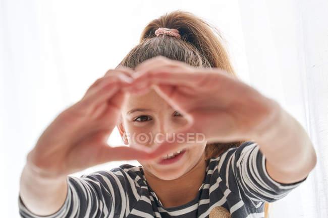 Glückliches kleines Mädchen lächelt und blickt in die Kamera durch Herzgeste vor weißem Hintergrund — Stockfoto