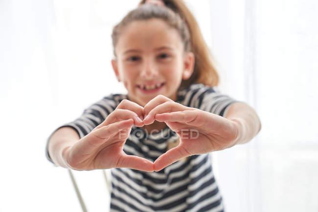Glückliches kleines Mädchen lächelt und blickt in die Kamera, als mache es eine Herzensgeste vor weißem Hintergrund — Stockfoto