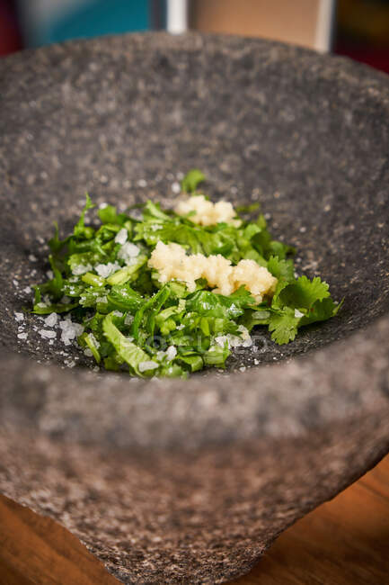 Fechar-se de argamassa maciça cinza cheio de verduras picadas e alho picado com sal colocado na mesa — Fotografia de Stock