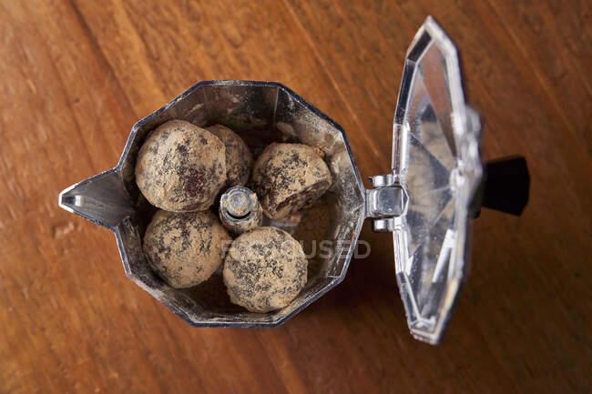 Von oben eine Kaffeemaschine aus rostfreiem Herd mit runden Kugeln köstlicher Schokoladentrüffel, serviert auf einem Tisch gegen eine Wand auf Graffiti — Stockfoto