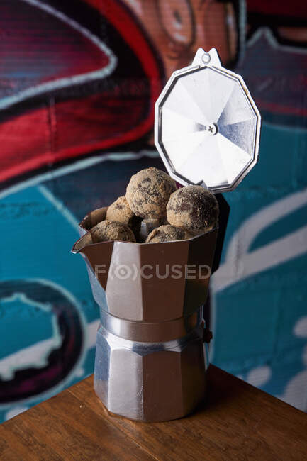 From above of stainless stove coffee maker with round balls of delicious chocolate truffles served on table against wall on graffiti — Stock Photo