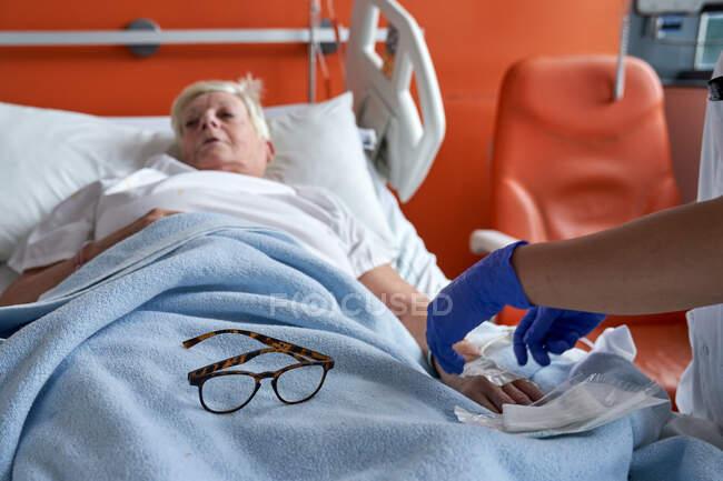 Enfermeira da colheita injetando medicação no braço do paciente maduro — Fotografia de Stock