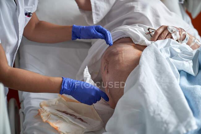 Enfermeira de cultura tendendo sutura de paciente idoso — Fotografia de Stock