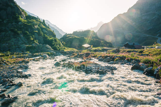 Powerful mountain river streaming through stones in bright sunny daytime in Switzerland — Stock Photo