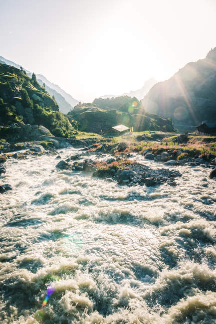 Powerful mountain river streaming through stones in bright sunny daytime in Switzerland — Fotografia de Stock