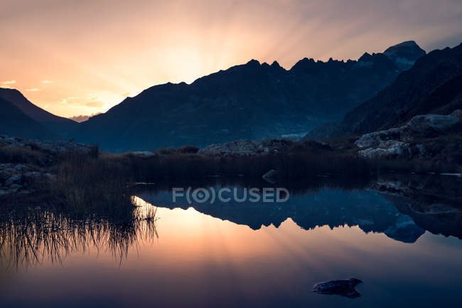 Breathtaking landscape of motionless water reflecting sky in warm sunset light and mountains in Switzerland — Stock Photo