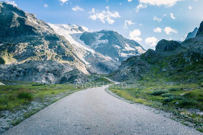 Спокойный пейзаж изгиба асфальтовой дороги в горах с зеленой травой в Швейцарии — стоковое фото
