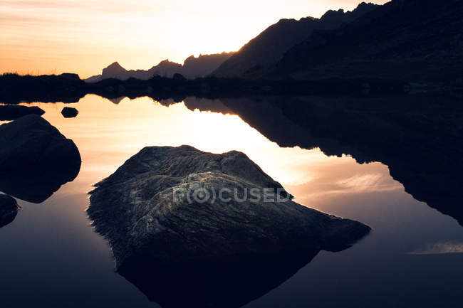 Breathtaking landscape of motionless water reflecting sky in warm sunset light and mountains in Switzerland — стокове фото