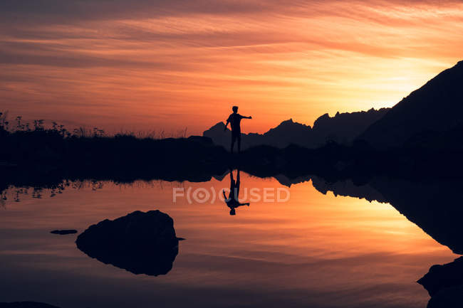 Silhouette of person balancing on shore and reflecting in calm water surrounded by mountains in Switzerland — стокове фото