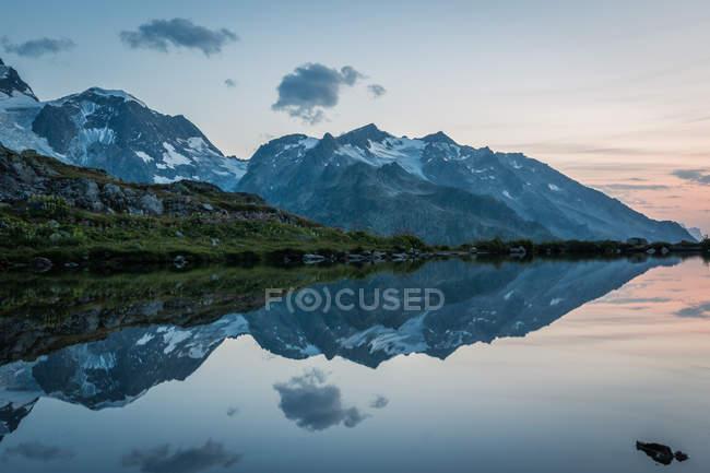 Côte vide d'un lac calme dans des montagnes enneigées reflétant le ciel en Suisse — Photo de stock